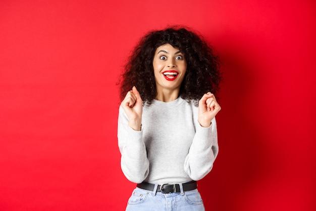 Opgewonden vrouw die prijs wint, zich verheugt en er gelukkig uitziet, verbaasd glimlacht, staande tegen een rode achtergrond