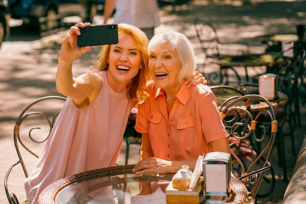 Opgewonden vrouw die smartphone vasthoudt en selfie neemt met haar bejaarde moeder