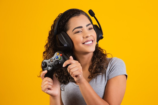 Opgewonden vrouw die videogame speelt op gele achtergrond.