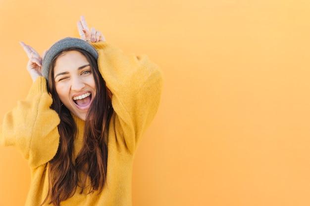 Opgewonden vrouw hoorn gebaar tonen tegen geel oppervlak