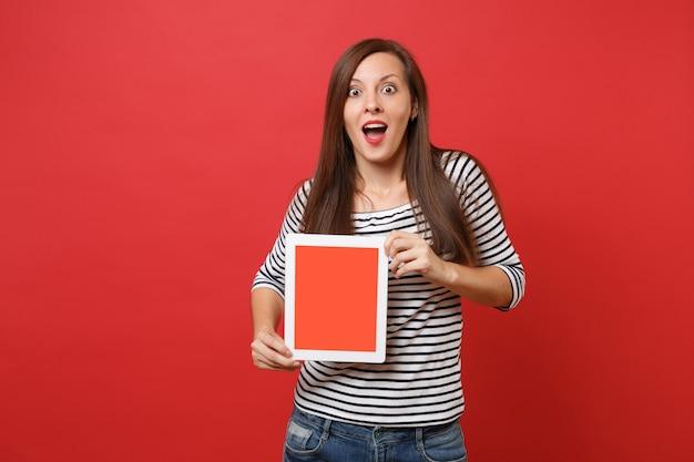 Opgewonden vrouw houdt mond wijd open en kijkt verrast greep tablet pc-computer met leeg zwart leeg scherm geïsoleerd op rode achtergrond. mensen oprechte emoties levensstijl concept. bespotten kopie ruimte.