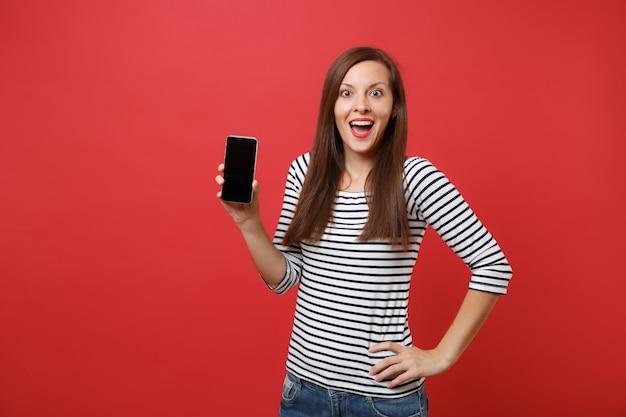 Opgewonden vrouw houdt mond wijd open, kijkt verrast, houdt mobiele telefoon vast met leeg zwart leeg scherm geïsoleerd op rode achtergrond. mensen oprechte emoties, lifestyle concept. bespotten kopie ruimte.