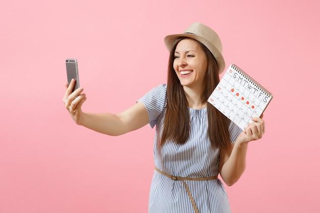 Opgewonden vrouw in blauwe jurk doet selfie op mobiele telefoon, met periodenkalender voor het controleren van menstruatiedagen geïsoleerd op roze achtergrond. medisch, gezondheidszorg, gynaecologisch concept. ruimte kopiëren.