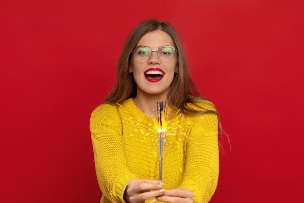 Opgewonden vrouw in bril met wonderkaarsen, draagt gele trui