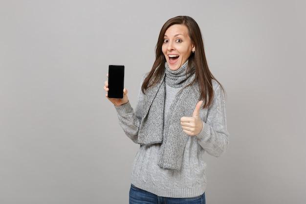 Opgewonden vrouw in grijze trui, sjaal duim opdagen, met mobiele telefoon met leeg leeg scherm geïsoleerd op een grijze achtergrond. gezonde mode levensstijl mensen oprechte emoties, koude seizoen concept.