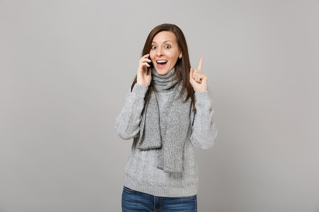 Opgewonden vrouw in grijze trui, sjaal met wijsvinger omhoog met geweldig nieuw idee, praten op mobiele telefoon geïsoleerd op een grijze achtergrond. gezonde mode-levensstijl, emoties van mensen, concept van het koude seizoen.