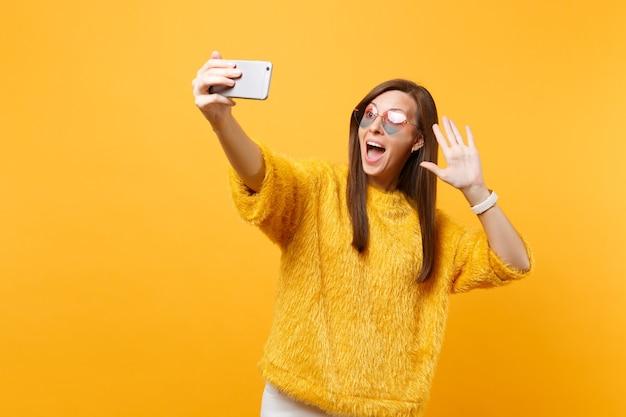 Opgewonden vrouw in hart bril doen selfie schot op mobiele telefoon maken video-oproep zwaaiende hand voor groet geïsoleerd op felgele achtergrond. mensen oprechte emoties, levensstijl. ruimte kopiëren.