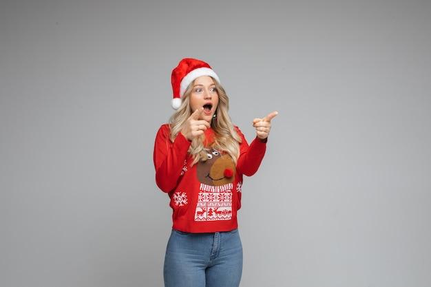 Opgewonden vrouw in kerstmuts wijzend op kopie ruimte.