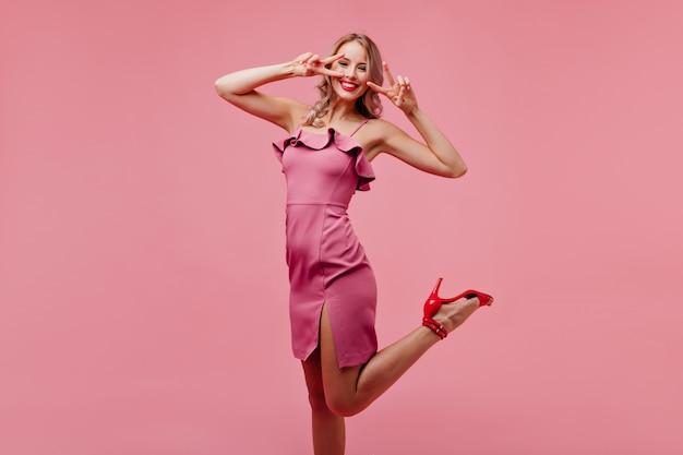 Opgewonden vrouw in roze outfit dansen met vrolijke glimlach