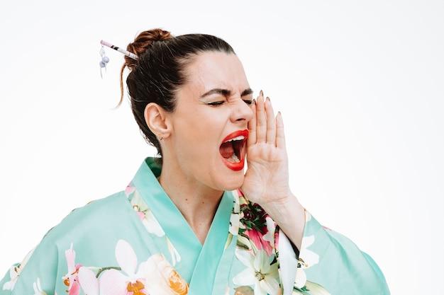 Opgewonden vrouw in traditionele japanse kimono die schreeuwt of iemand belt die de hand in de buurt van de mond houdt op wit