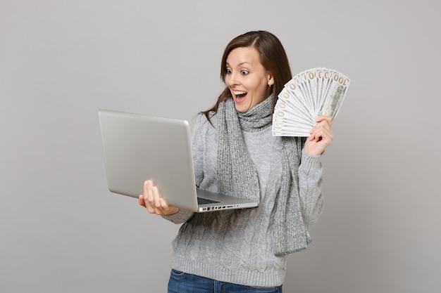 Opgewonden vrouw in trui die op laptop pc werkt, houdt veel dollars bankbiljetten contant geld geïsoleerd op een grijze achtergrond. gezonde levensstijl, online behandelingsadvies, concept voor het koude seizoen.