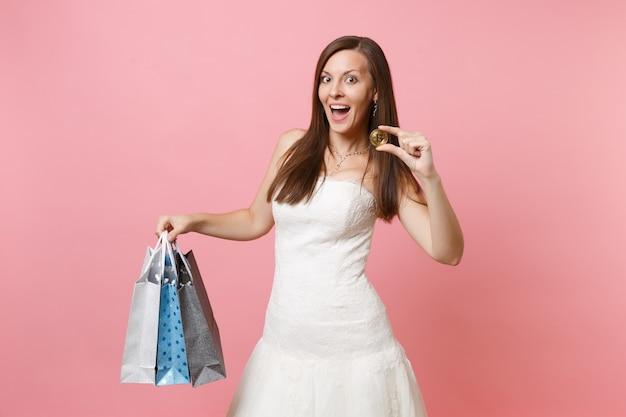 Opgewonden vrouw in witte jurk houdt bitcoin metalen munt van gouden kleur, multi gekleurde pakketten tas met aankopen na het winkelen