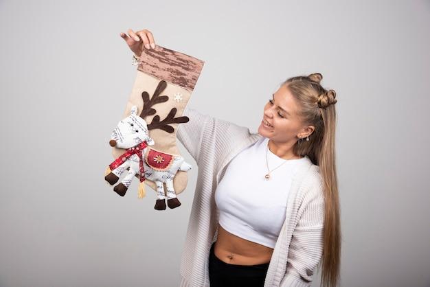 Opgewonden vrouw kijken naar christmas stocking op grijze achtergrond.