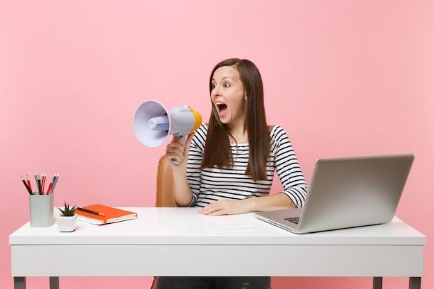 Opgewonden vrouw kijkt opzij schreeuwend in megafoon terwijl ze aan het project werkt aan een wit bureau op kantoor met pc-laptop geïsoleerd op een pastelroze achtergrond. prestatie zakelijke carrière concept. ruimte kopiëren.