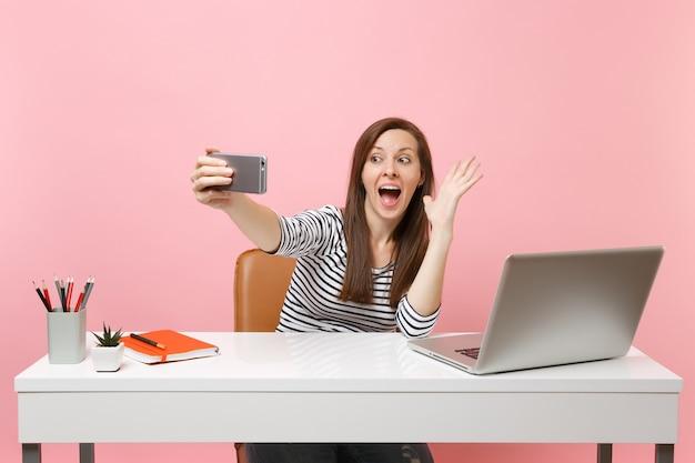 Opgewonden vrouw maakt video-oproep zwaaiende hand voor groet doen selfie schot op mobiele telefoon terwijl zitten werk aan bureau met laptop geïsoleerd op roze achtergrond. prestatie zakelijke carrière. ruimte kopiëren.