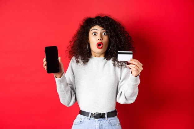 Opgewonden vrouw met creditcard die een leeg smartphonescherm toont, verbaasd naar adem snakkend, staande tegen een rode achtergrond.