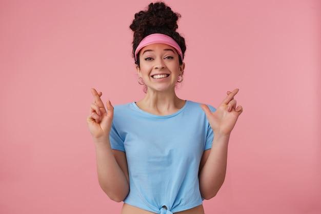 Opgewonden vrouw met donker krullend haarbroodje. ik draag een roze klep, oorbellen en een blauw t-shirt. heeft make-up. houdt de vingers gekruist, een wens doen