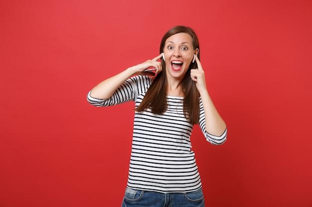 Opgewonden vrouw met draadloze oortelefoons die de mond wijd open houden en verbaasd kijken met het luisteren naar muziek op een rode achtergrond. mensen oprechte emoties, levensstijl. bespotten kopie ruimte.