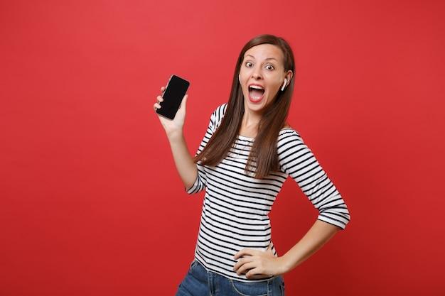 Opgewonden vrouw met draadloze oortelefoons die de mond wijd open houden, met een mobiele telefoon met een leeg zwart leeg scherm geïsoleerd op een rode achtergrond. mensen oprechte emoties, levensstijl. bespotten kopie ruimte.
