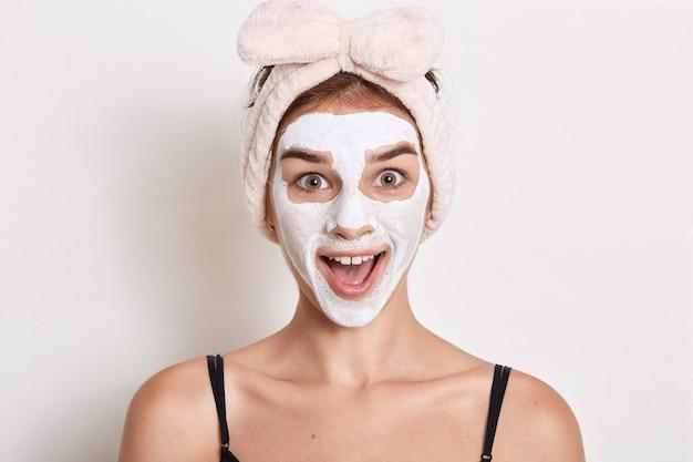 Opgewonden vrouw met hoofdband met strik direct kijken naar camera met verbaasde gezichtsuitdrukking, dame kijkt verbaasd, staat met grote ogen.