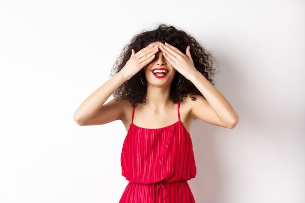 Opgewonden vrouw met krullend haar in feestjurk, ogen sluiten en lachend met rode lippen, wachtend op verrassing met blij gezicht, staande op een witte achtergrond.