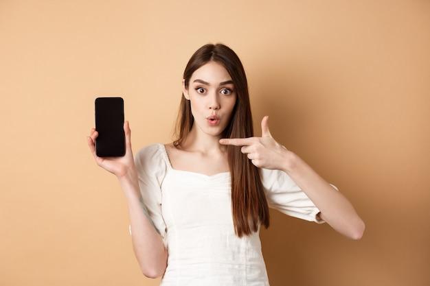 Opgewonden vrouw met nieuws op het scherm, wijzend op lege telefoon en verbaasd, staande op beige achtergrond.