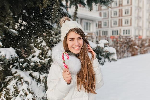 Opgewonden vrouw met sluik bruin haar, plezier in besneeuwde dag en genieten van fotoshoot. outdoor portret van prachtige witte dame in trendy kleding poseren met kerstsnoepjes.