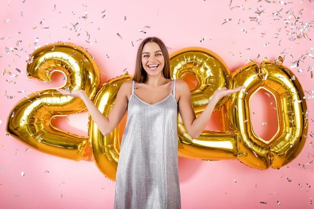Opgewonden vrouw met zilveren confetti en gouden 2020 nieuwe jaar ballonnen geïsoleerd over roze
