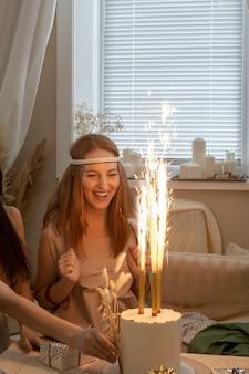 Opgewonden vrouw moderne hippie mode kleding viert verjaardag met petard fire cake geschenkdozen