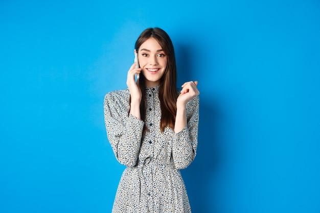 Opgewonden vrouw ontvangt goed nieuws op mobiele telefoon, glimlachend gelukkig, pratend op smartphone, staande op blauw.