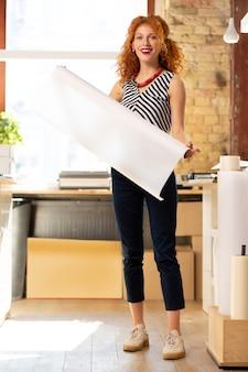 Opgewonden vrouw. opgewonden vrouw met een gestreepte blouse die werkt in een uitgeverij met een papierrol