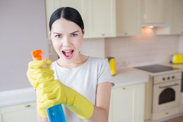 Opgewonden vrouw staat en houdt blauwe spray in handen. ze richt het op de camera. meisje staat in de keuken.