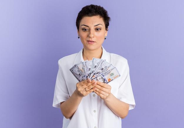 Opgewonden vrouw van middelbare leeftijd die geld vasthoudt en bekijkt