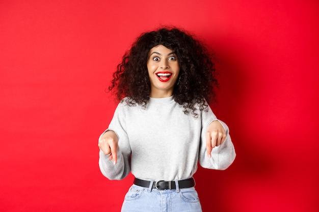 Opgewonden vrouw wijzende vingers naar beneden en glimlachend verbaasd, kijk hier gebaar, logo op rode lege ruimte weergegeven.