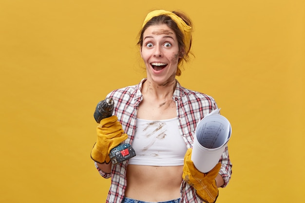 Opgewonden vrouwelijke arbeider kijkt met afgeluisterde ogen vol geluk en geopende mond terwijl ze gepromoveerd wordt met boormachine en blauwdruk in haar handen geïsoleerd over gele muur
