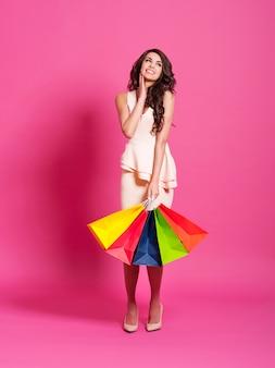 Opgewonden vrouwelijke shopaholic met boodschappentassen