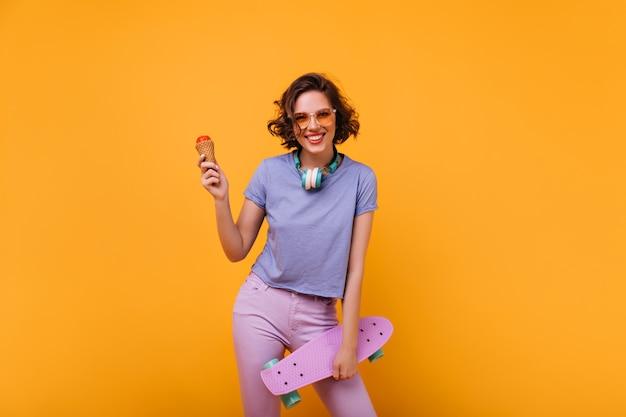 Opgewonden vrouwelijke skateboarder die ijs eet. binnenfoto van extatisch krullend meisje met klein paars longboard.