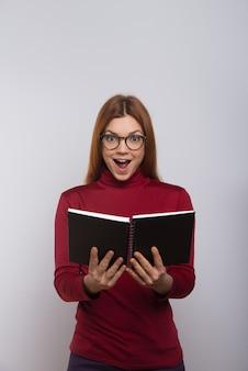 Opgewonden vrouwelijke student leesboek