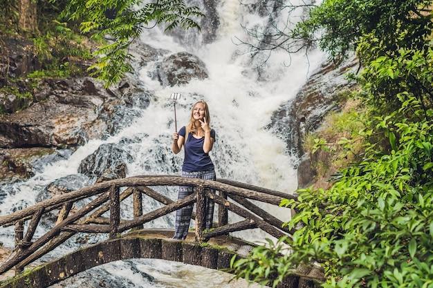 Opgewonden vrouwelijke toerist die zelfportret voor de waterval maakt