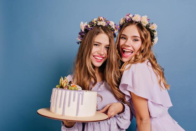 Opgewonden vrouwen poseren met cake en lachen op blauwe muur
