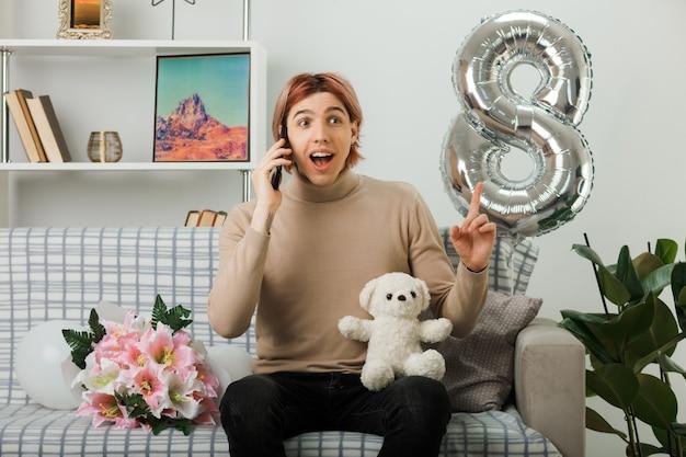 Opgewonden wijst naar een knappe man op een gelukkige vrouwendag die een teddybeer vasthoudt en spreekt aan de telefoon terwijl hij op de bank in de woonkamer zit