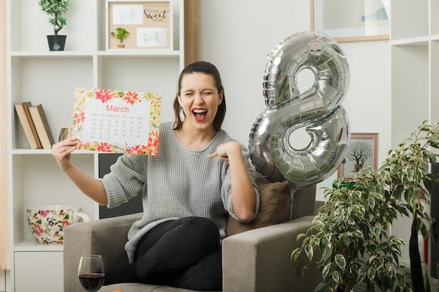 Opgewonden wijst naar zichzelf mooie vrouw op gelukkige vrouwendag met kalender zittend op een fauteuil in de woonkamer