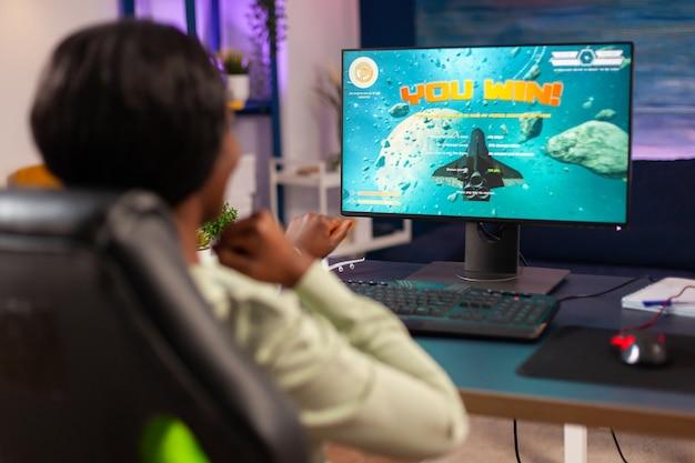 Opgewonden winnaar wining space shooter e sport competitie concurrerende speler met joystick voor online kampioenschap zittend op een gamestoel 's avonds laat