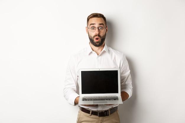 Opgewonden zakenman die iets op het scherm van de laptop laat zien, gelukkig over een witte achtergrond