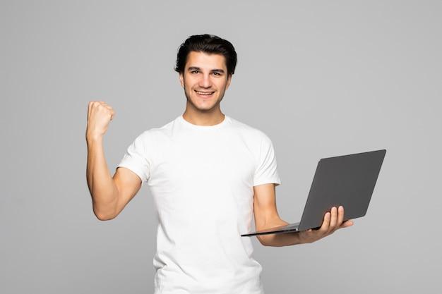 Opgewonden zakenman die naar het laptopscherm kijkt met wijd open mond, zijn overwinning vierend op grijs