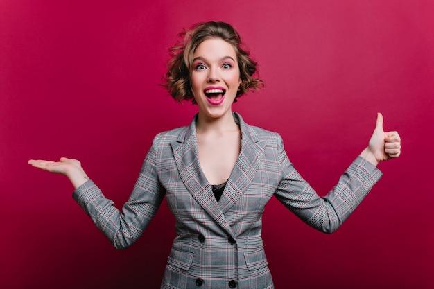 Opgewonden zakenvrouw in elegante grijze kleding met plezier tijdens fotoshoot. enthousiast meisje in formele stijl jas zwaaiende handen op bordeaux muur.