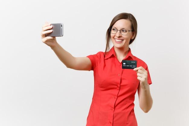 Opgewonden zakenvrouw in rood shirt doen selfie schot op mobiele telefoon met creditcard, giraal geld geïsoleerd op een witte achtergrond. onderwijs onderwijzen in het concept van de middelbare school universiteit.