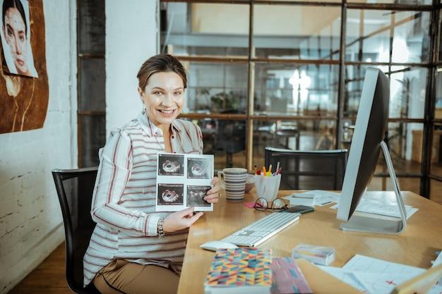 Opgewonden zijn. vrolijke zwangere vrouw voelt zich opgewonden terwijl ze haar echografie-onderzoek vasthoudt