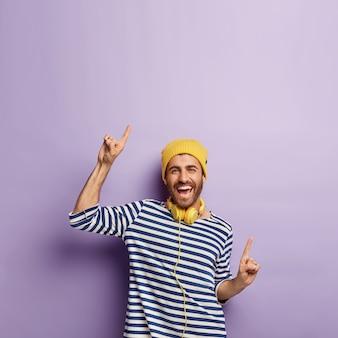 Opgewonden zorgeloze positieve man in casual gestreepte trui, gele hoed, wijst vrolijk omhoog op geweldige kopie ruimte voor je promo