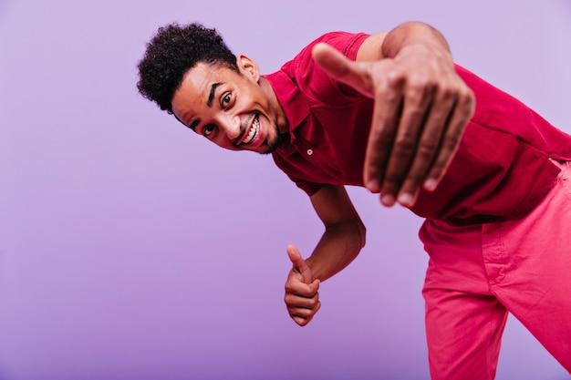 Opgewonden zwart mannelijk model dansen. grappige emotionele man die in rood t-shirt met glimlach kijkt.